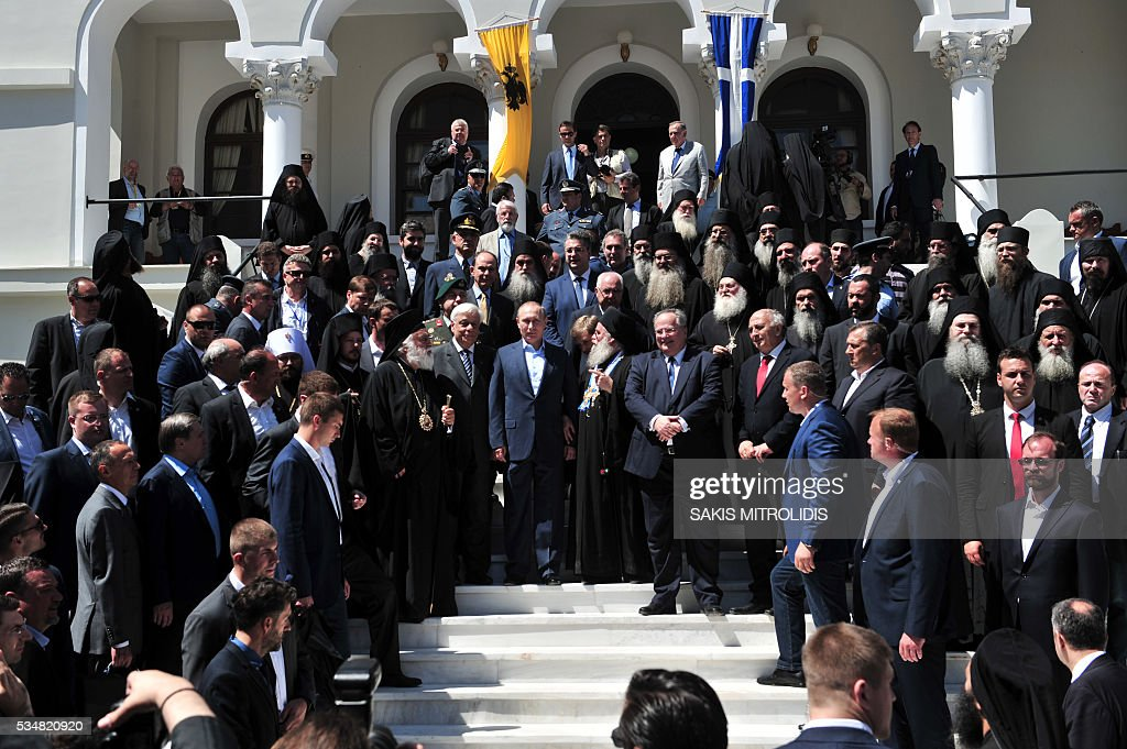 Russian President Vladimir Putin (C) and Greek President Prokopis Pavlopoulos (C-L) pose during a visit to the monastic community of Mount Athos, in Karyes on May 28, 2016. Putin, who has often talked about his strong Orthodox faith, will join celebrations for the 1,000th anniversary of the Russian presence at the ancient, all-male monastic community of Mount Athos. The visit, Putin's first to the EU since December, comes at a low ebb in relations between Russia and Europe over the conflict in Ukraine that broke out in 2014, with sanctions still in force against Moscow. / AFP / SAKIS