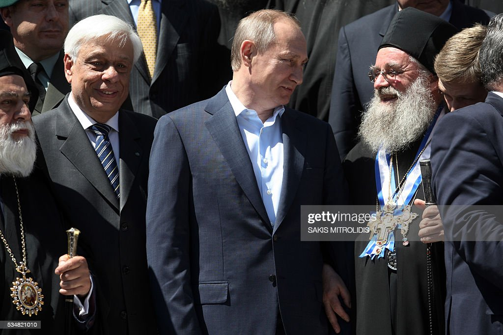 Russian President Vladimir Putin (C) and Greek President Prokopis Pavlopoulos (L) pose during a visit to the monastic community of Mount Athos, in Karyes on May 28, 2016. Putin, who has often talked about his strong Orthodox faith, will join celebrations for the 1,000th anniversary of the Russian presence at the ancient, all-male monastic community of Mount Athos. The visit, Putin's first to the EU since December, comes at a low ebb in relations between Russia and Europe over the conflict in Ukraine that broke out in 2014, with sanctions still in force against Moscow. / AFP / SAKIS