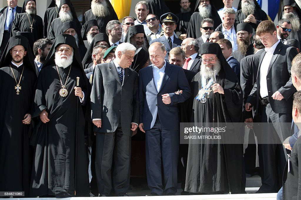 Russian President Vladimir Putin (C) and Greek President Prokopis Pavlopoulos (3R) pose during a visit to the monastic community of Mount Athos, in Karyes on May 28, 2016. Putin, who has often talked about his strong Orthodox faith, will join celebrations for the 1,000th anniversary of the Russian presence at the ancient, all-male monastic community of Mount Athos. The visit, Putin's first to the EU since December, comes at a low ebb in relations between Russia and Europe over the conflict in Ukraine that broke out in 2014, with sanctions still in force against Moscow. / AFP / SAKIS