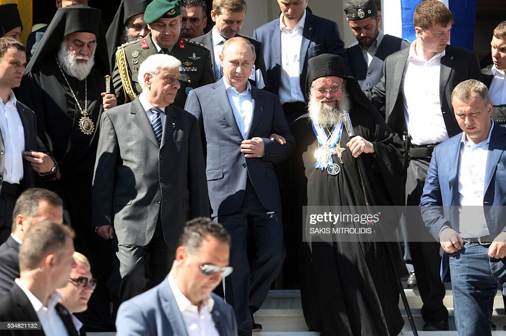 Russian President Vladimir Putin (C) and Greek President Prokopis Pavlopoulos (L) walk down stairs during a visit to the monastic community of Mount Athos, in Karyes on May 28, 2016. Putin, who has often talked about his strong Orthodox faith, will join celebrations for the 1,000th anniversary of the Russian presence at the ancient, all-male monastic community of Mount Athos. The visit, Putin's first to the EU since December, comes at a low ebb in relations between Russia and Europe over the conflict in Ukraine that broke out in 2014, with sanctions still in force against Moscow. / AFP / SAKIS