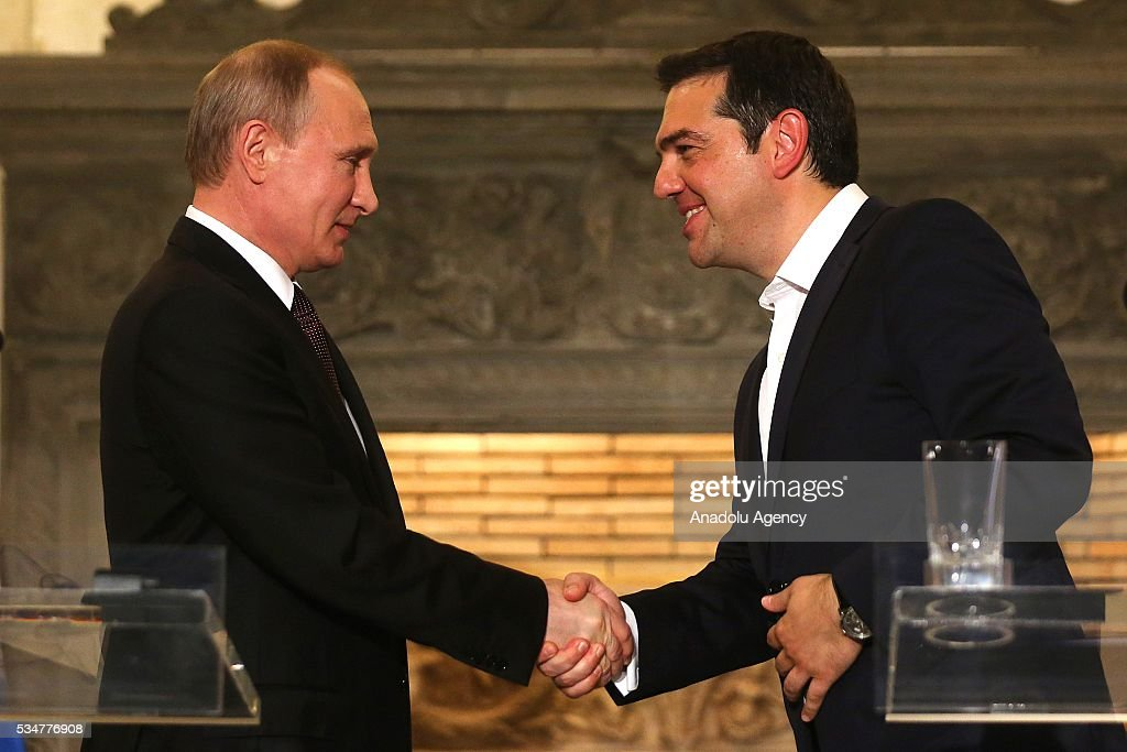 Russian President Vladimir Putin (L) and Greek Prime Minister Alexis Tsipras (R) shake hands after they hold a joint press conference following their meeting in Athens, Greece on May 27, 2016.