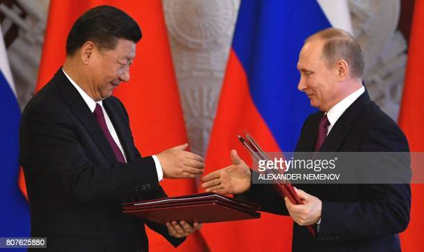 Russian President Vladimir Putin and his Chinese counterpart Xi Jinping shake hands during a signing ceremony in the Kremlin in Moscow on July 4 2017...