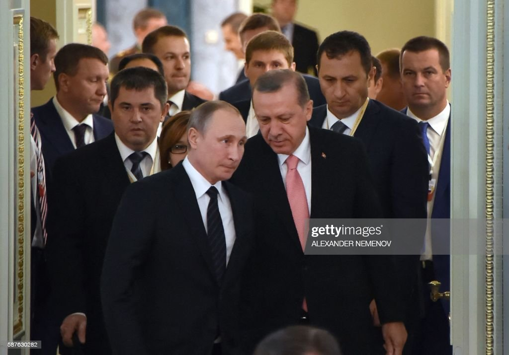 Russian President Vladimir Putin and his Turkish counterpart Recep Tayyip Erdogan enter a hall to start their meeting with Russian and Turkish...