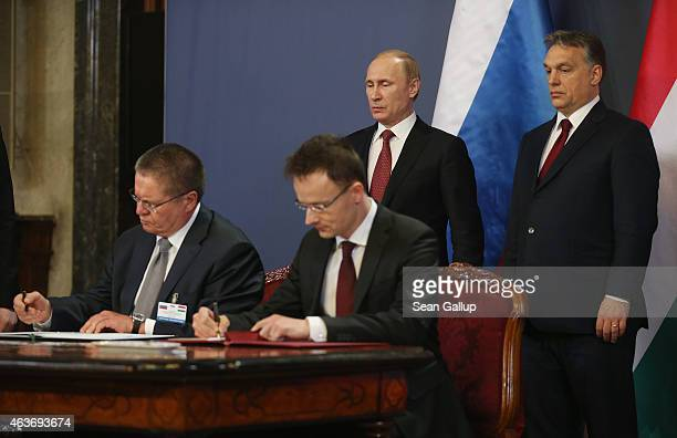 Russian President Vladimir Putin and Hungarian Prime Minister Viktor Orban look on as members of their respective delgations sign agreements between...