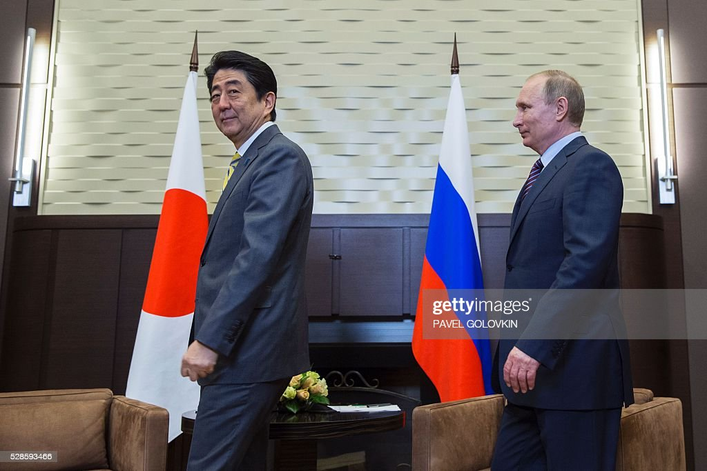 Russian President Vladimir Putin (R) and Japanese Prime Minister Shinzo Abe enter a hall before a meeting at the Bocharov Ruchei state residence in Sochi on May 6, 2016. / AFP / POOL / Pavel Golovkin