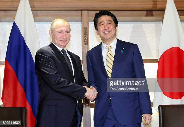Russian President Vladimir Putin and Japanese Prime Minister Shinzo Abe shake hands prior to their meeting on December 15 2016 in Nagato Yamaguchi...