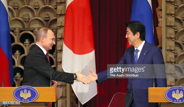 Russian President Vladimir Putin and Japanese Prime Minister Shinzo Abe shakes hands during a joint press conference following their meeting at Abe's...