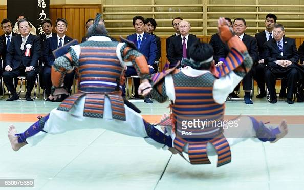 Russian President Vladimir Putin and Japanese Prime Minister Shinzo Abe look at performance of ancient custom judo beside Vice Chairman of the All...