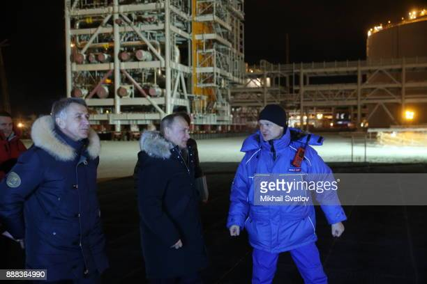 Russian President Vladimir Putin and Novatek CEO Leonid Michelson listens to a worker while visiting the LNG plant in Sabetta sea port at Yamal...