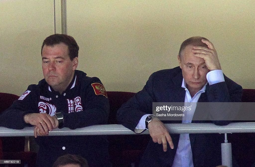 Russian President Vladimir Putin (R) and Prime Minister Dmitry Medvedev (L) watch Russia vs Slovakia ice hockey match at the 2014 Winter Olympics February 16, 2014 in Sochi, Russia. Putin is on a three-days visit to the 2014 Winter Olypmic games.