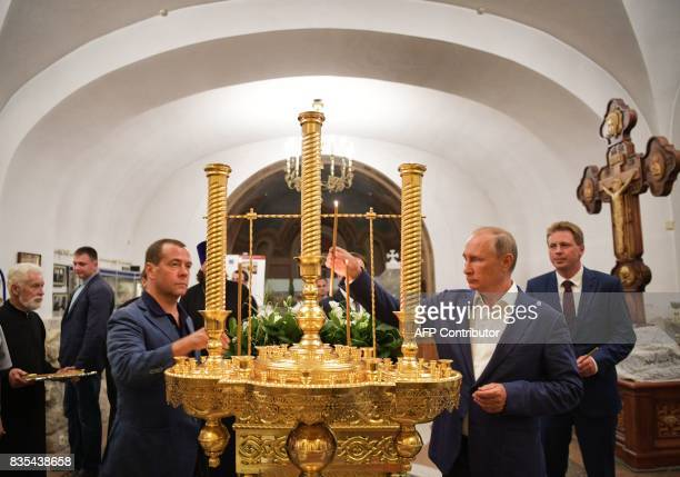 Russian President Vladimir Putin and Prime Minister Dmitry Medvedev light candles as they visit the Saint Vladimir's Cathedral in the ancient city of...