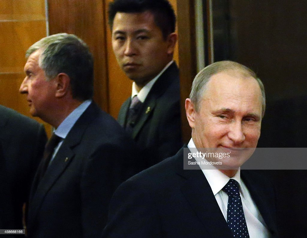 Russian President Vladimir Putin (C) and Rosneft President Igor Sechin (L) arrive by the elevator to the Russian-Japanese meeting during the Asia-Pacific Economic Cooperation (APEC) summit on November 9, 2014 in Beijing, China. 2014 APEC Economic Leaders' Meetings and APEC summit is being held at Beijing's outskirt Yanqi Lake.