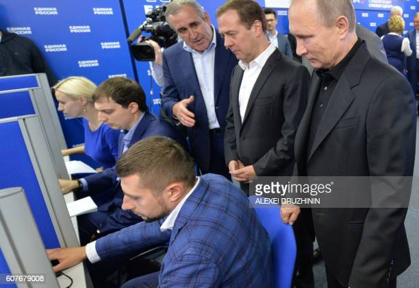 TOPSHOT Russian President Vladimir Putin and Russian Prime Minister and chairman of the United Russia political party Dmitry Medvedev visit the...