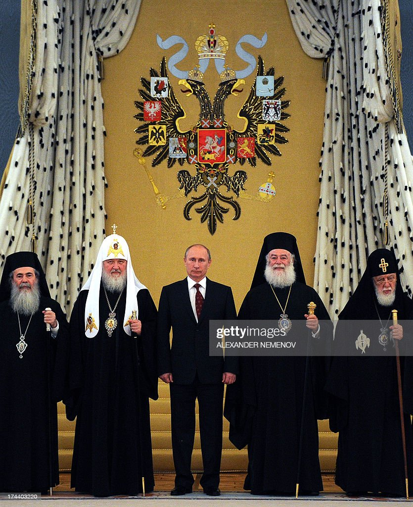 Russian President Vladimir Putin (C) and Russia's Patriarch Kiril (2ndR) pose for a family photo during the meeting with Orthodox leaders at the Kremlin in Moscow on July 25, 2013.