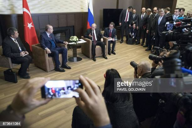 Russian President Vladimir Putin and Turkish President Recep Tayyip Erdogan speak during their meeting in the Bocharov Ruchei state residence in the...