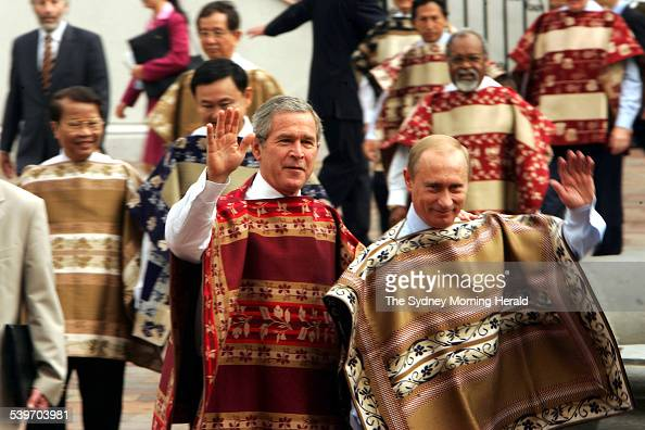Russian President Vladimir Putin and United States President George Bush wave as leaders from the Pacific Rim pose for a photocall wearing the...