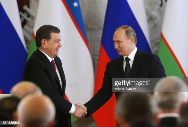 Russian President Vladimir Putin and Uzbek President Shavkat Mirziyoyev shake hands at the signing ceremony at the Grand Kremlin Palace on April 5...