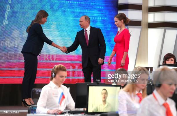 Russian President Vladimir Putin answers shakes hands with TV host as he arrives at the Gostiny Dvor studio during the annual 'Direct Line with...