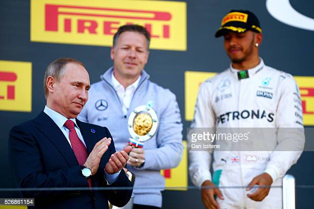 Russian President Vladimir Putin applauds as he stands on the podium next to Lewis Hamilton of Great Britain and Mercedes GP after the Formula One...