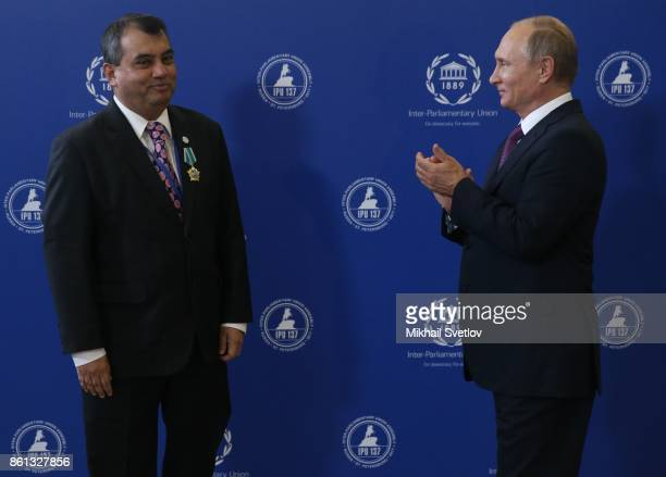 Russian President Vladimir Putin applauds as IPU President Saber Hossen Chowdhury looks on during the opening of 137th InterParliamentary Union...