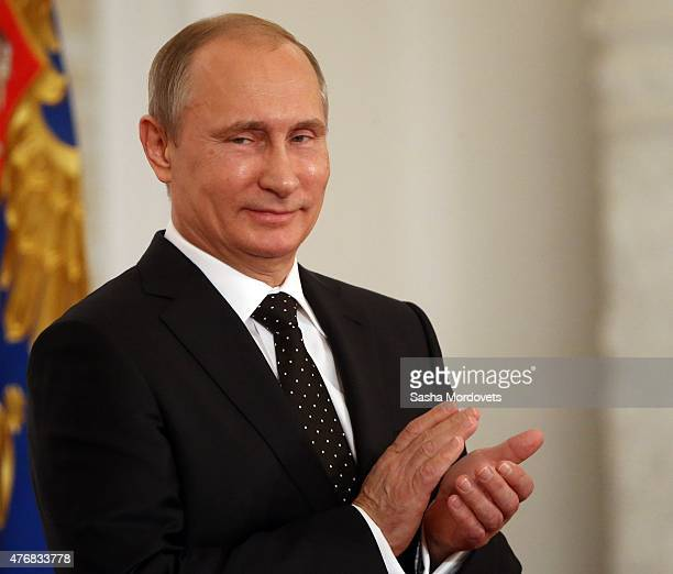 Russian President Vladimir Putin applauds during a presentation ceremony of state awards marking the Day of Russia in the Grand Kremlin Palace in...