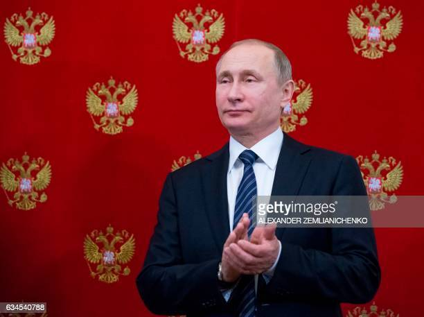 Russian President Vladimir Putin applauds during a signing ceremony following his talks with Slovenian President at the Kremlin in Moscow on February...