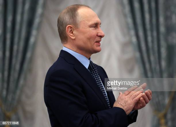 Russian President Vladimir Putin applauds during the awards ceremony at the Kremlim on March 2017 in Moscow Russia has awarded 6 people including 6...