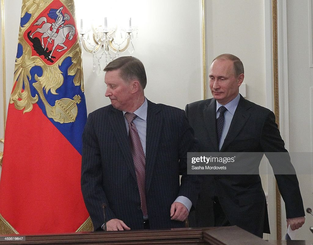 Russian President Vladimir Putin arrives as Head of the Presidential Administration Sergei Ivanov looks on during the meeting with members of the...