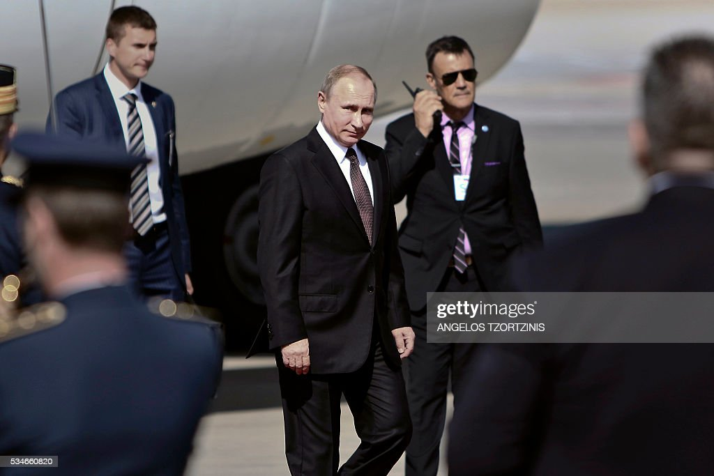 Russian President Vladimir Putin (C) arrives at the Athens international Airport, on May 27, 2016, at the start of his trip to Greece aiming to reinforce a relationship with one of his few friends in the EU amid continuing diplomatic tensions with the West. / AFP / ANGELOS