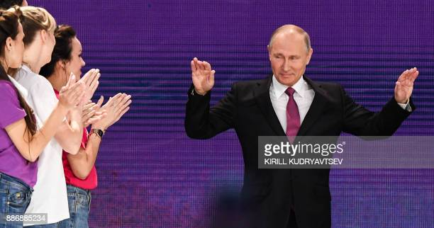 TOPSHOT Russian President Vladimir Putin arrives to give a speech at a forum of volunteers in Moscow on December 6 2017 / AFP PHOTO / Kirill...