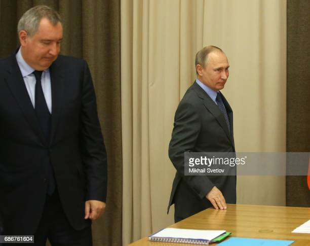 Russian President Vladimir Putin arrives to the meeting with top managers of space industry sector as Deputy Prime Minister Dmitry Rogozin looks on...