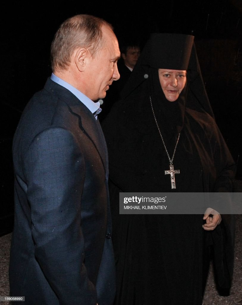 Russian President Vladimir Putin attends a Christmas service in a church in Sochi early on January 7, 2013. Orthodox Christians celebrate Christmas on January 7 in the Middle East, Russia and other Orthodox churches that use the old Julian calendar instead of the 17th-century Gregorian calendar adopted by Catholics, Protestants, Greek Orthodox and commonly used in secular life around the world. AFP PHOTO/ RIA-NOVOSTI/ MIKHAIL KLIMENTIEV