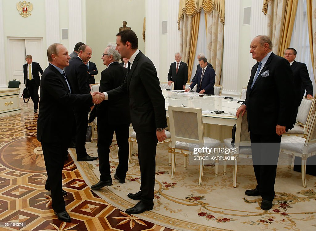 Russian President Vladimir Putin (L) attends a meeting with French businessmen at the Kremlin in Moscow on May 25, 2016. / AFP / POOL / SERGEI