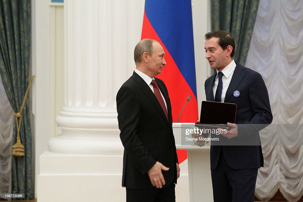 Russian President <a gi-track='captionPersonalityLinkClicked' href=/galleries/search?phrase=Vladimir+Putin&family=editorial&specificpeople=154896 ng-click='$event.stopPropagation()'>Vladimir Putin</a> (L) awards actor Konstantin Khabensky, who wears a badge that reads 'Children are outside politics!,' the title of People's Artist of Russia during an awards ceremony at the Kremlin on December 26, 2012 in Moscow, Russia. Putin awarded 40 actors, scientists, writers and other people in an annual ceremony for achievements in 2012. The Russian parliament has proposed a bill that will ban Americans from adopting Russian children.