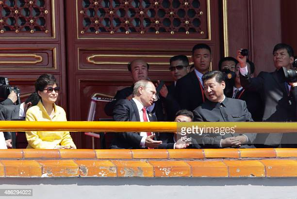 Russian President Vladimir Putin chats with China's President Xi Jinping next to South Korean President Park Geunhye on Tiananmen Gate during the...