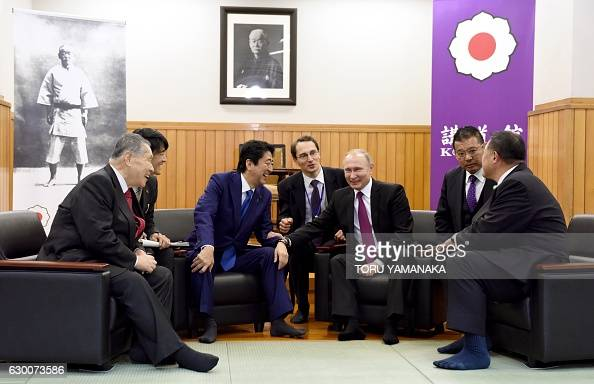 TOPSHOT Russian President Vladimir Putin chats with Japanese Prime Minister Shinzo Abe former Japanese Prime Minister Yoshiro Mori and vice chairman...