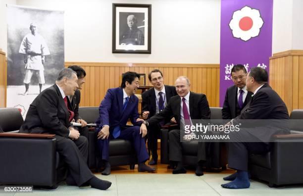 TOPSHOT Russian President Vladimir Putin chats with Japanese Prime Minister Shinzo Abe former Japanese Prime Minister Yoshiro Mori and vice chairman...