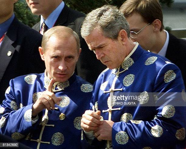 Russian President Vladimir Putin chats with US President George W Bush donning traditional Chinese silk coats as they walk to a family photo session...