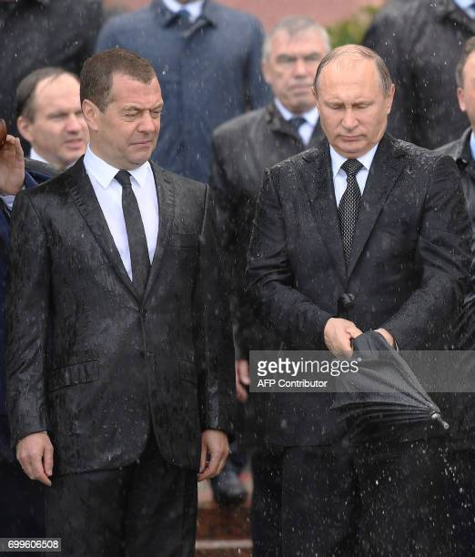 Russian President Vladimir Putin closes an umbrella under pouring rain next to Prime Minister Dmitry Medvedev during a wreathlaying ceremony marking...