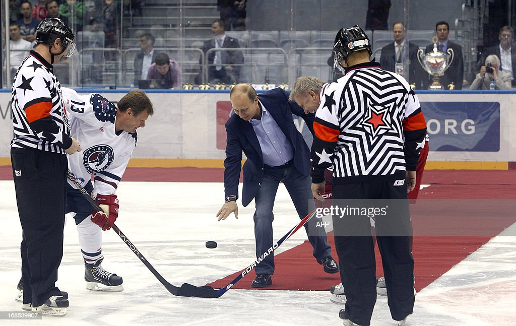 Russian President Vladimir Putin (C) drops the puck to start an ice hockey match during a festival of Russian amateur ice hockey at the Bolshoy ice dome, the hockey venue for the Sochi 2014 Winter Olympics, in the Olympic Park in Adler, near Sochi on May 10, 2013. AFP PHOTO / POOL / SERGEI KARPUKHIN