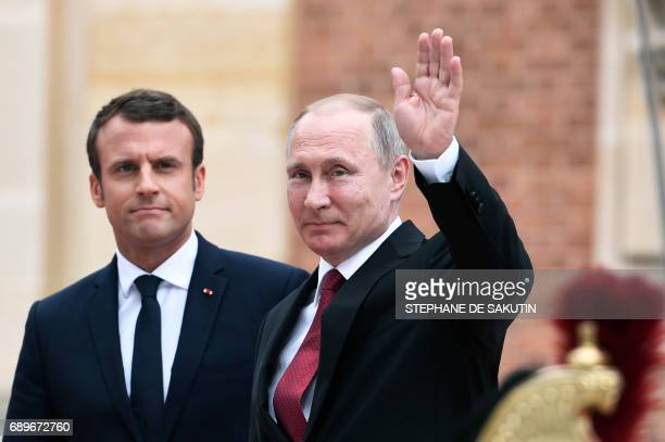 Russian President Vladimir Putin flanked by French President Emmanuel Macron waves upon his arrival at the Versailles Palace near Paris on May 29...