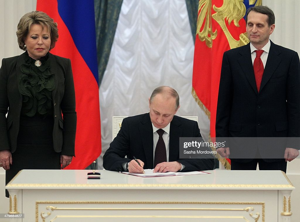 Russian President <a gi-track='captionPersonalityLinkClicked' href=/galleries/search?phrase=Vladimir+Putin&family=editorial&specificpeople=154896 ng-click='$event.stopPropagation()'>Vladimir Putin</a> flanked by Upper House Speaker <a gi-track='captionPersonalityLinkClicked' href=/galleries/search?phrase=Valentina+Matviyenko&family=editorial&specificpeople=582974 ng-click='$event.stopPropagation()'>Valentina Matviyenko</a> (L) and State Duma Speacker <a gi-track='captionPersonalityLinkClicked' href=/galleries/search?phrase=Sergei+Naryshkin&family=editorial&specificpeople=2665931 ng-click='$event.stopPropagation()'>Sergei Naryshkin</a> (R) signs final decree completing annexation of Crimea at the Kremlin on March 21, 2014 in Moscow, Russia. Putin completed the legal process of making Crimea part of Russia.