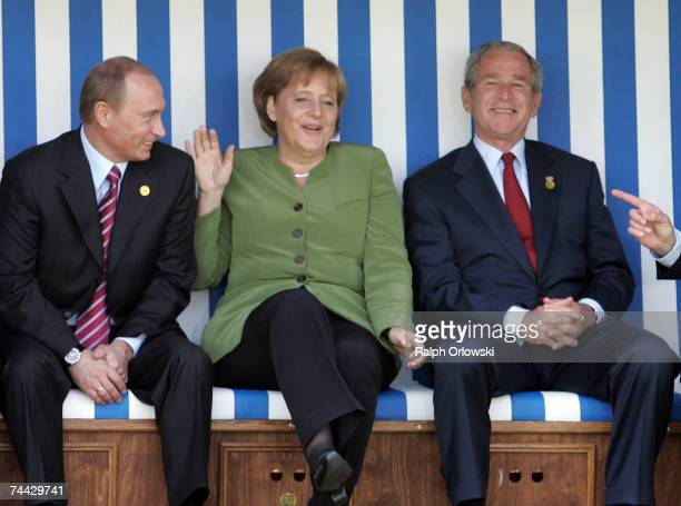 Russian President Vladimir Putin German Chancellor Angela Merkel and US President George W Bush joke as they sit in a beach chair during the first...