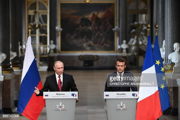Russian President Vladimir Putin gestures as he delivers a speech during a joint press conference with French President Emmanuel Macron following...