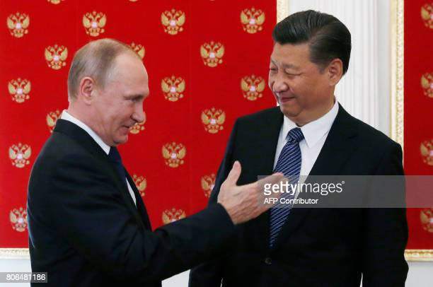 Russian President Vladimir Putin gestures as he welcomes China's President Xi Jinping during an informal meeting in the Kremlin in Moscow on July 3...