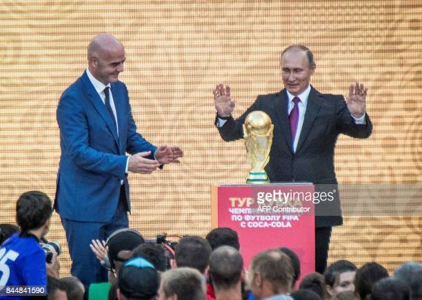 Russian President Vladimir Putin gestures next to the FIFA World Cup Trophy flanked by FIFA President Gianni Infantino during the opening of the...