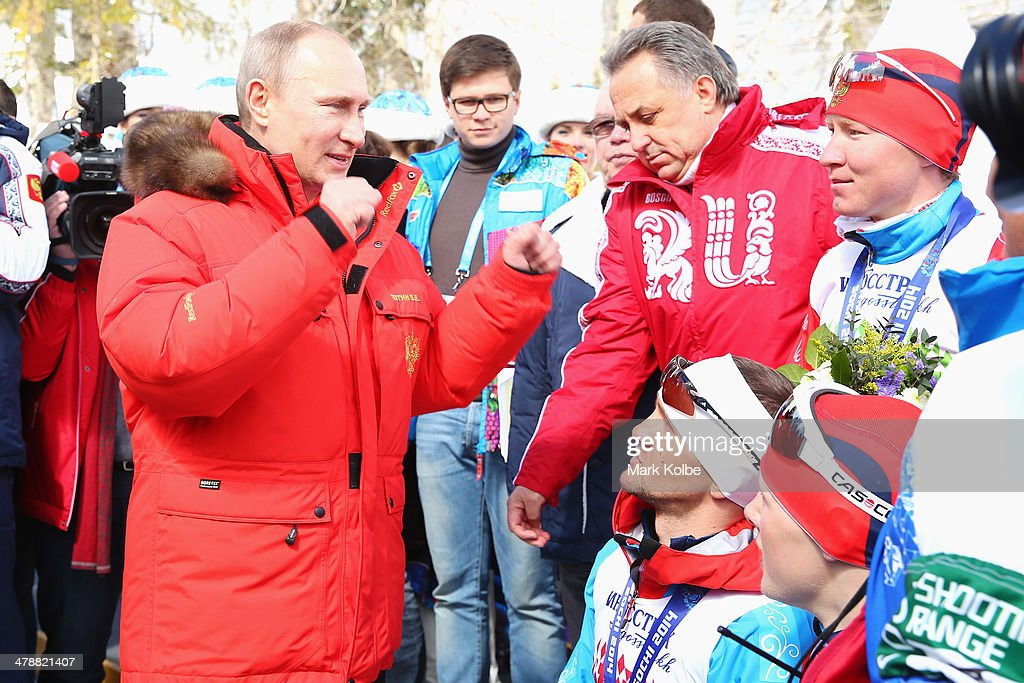 Russian President Vladimir Putin gestures to Roman Petushkov and Vladislav Lekomtcev of Russia and their team after their victory in the 4 x 2.5km Open Relay cross-country on day eight of the Sochi 2014 Paralympic Winter Games at Laura Cross-country Ski & Biathlon Center on March 15, 2014 in Sochi, Russia.