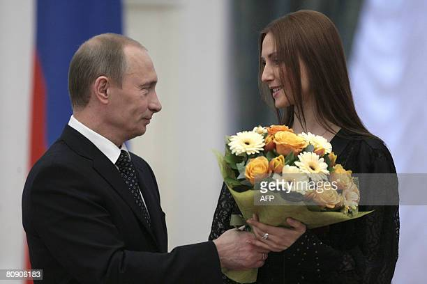 Russian President Vladimir Putin gives a bouquet of flowers to ballerina Svetlana Zakharova at a state awards ceremony at the Kremlin in Moscow on...