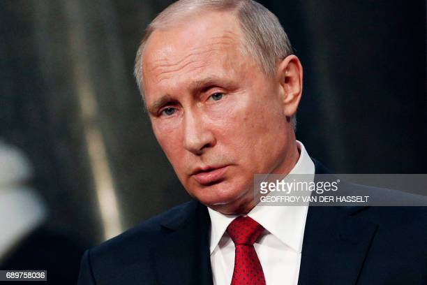 Russian President Vladimir Putin gives a joint press conference with the French president following their meeting at the Versailles Palace near Paris...
