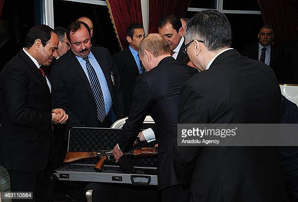 Russian President Vladimir Putin gives an AK47 rifle as a gift to Egyptian President Abdel Fattah elSisi during an informal dinner in honor of Putin...
